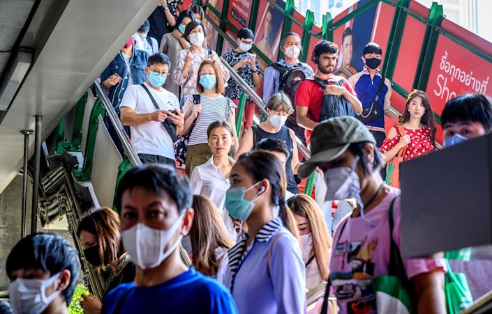 TOPSHOT - People with face masks arrive at a BTS Sky train station in Bangkok on January 27, 2020. - Thailand has detected eight Coronavirus cases so far -- three of whom are receiving treatment in hospital and five of whom have been discharged, according to a statement from Health Minister Anutin Charnvirakul: (Photo by MLADEN ANTONOV/AFP via Getty Images)