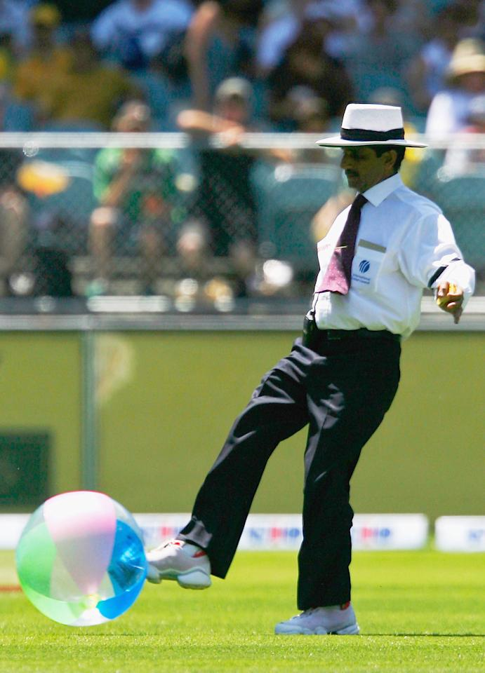 MELBOURNE, AUSTRALIA - DECEMBER 27:  Umpire Asad Rauf removes a beach ball from the arena during day two of the Second Test between Australia and South Africa played at the MCG on December 27, 2005 in Melbourne, Australia.   (Photo by Kristian Dowling/Getty Images)