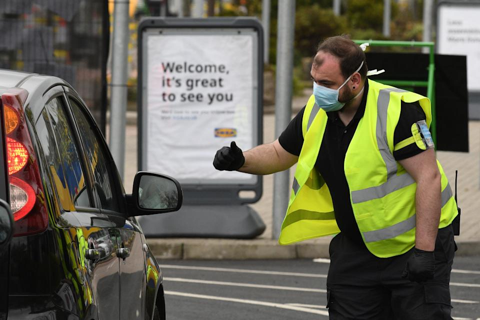 Stewards direct NHS staff visiting the drive-through COVID-19 testing centre set up at the car park of the Ikea store in Gateshead, northeast England on April 9, 2020 as Britain continued to battle the outbreak of new coronavirus and the governement prepared to extend the nationwide lockdown. - The disease has struck at the heart of the British government, infected more than 60,000 people nationwide and killed over 7,000, with another record daily death toll of 938 reported on April 8. A testing centre opened in Gateshead on April 9, 2020 as the government ramped up its testing of NHS staff for the new coronavirus. (Photo by Oli SCARFF / AFP) (Photo by OLI SCARFF/AFP via Getty Images)