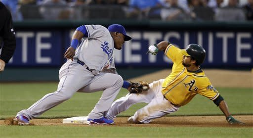 Oakland Athletics' Coco Crisp, right, safely steals third base as Los Angeles Dodgers third baseman Juan Uribe, left, makes a tag during the fourth inning of their baseball game in Oakland, Calif., Tuesday, June 19, 2012. (AP Photo/Eric Risberg)
