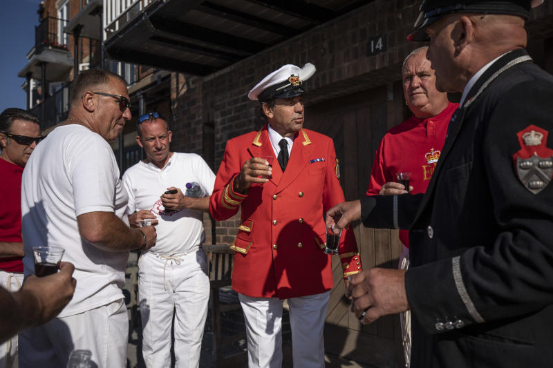 LONDON, ENGLAND - JULY 16: The Sovereign's Swan Marker, David Barber, (centre) makes a toast with members of the Vintners and Dyers teams ahead of the start of day two of the annual Swan Upping census on July 16, 2019 on the River Thames, South West London. The historic Swan Upping ceremony dates back to the 12th century, when the Crown claimed ownership of all Mute Swans and they were eaten at banquets and feasts. The Sovereign's Swan Marker, David Barber, counts the number of young cygnets on the river each year and ensures that the swan population is maintained. The swans and young cygnets are also assessed for any signs of injury or disease. (Photo by Dan Kitwood/Getty Images)
