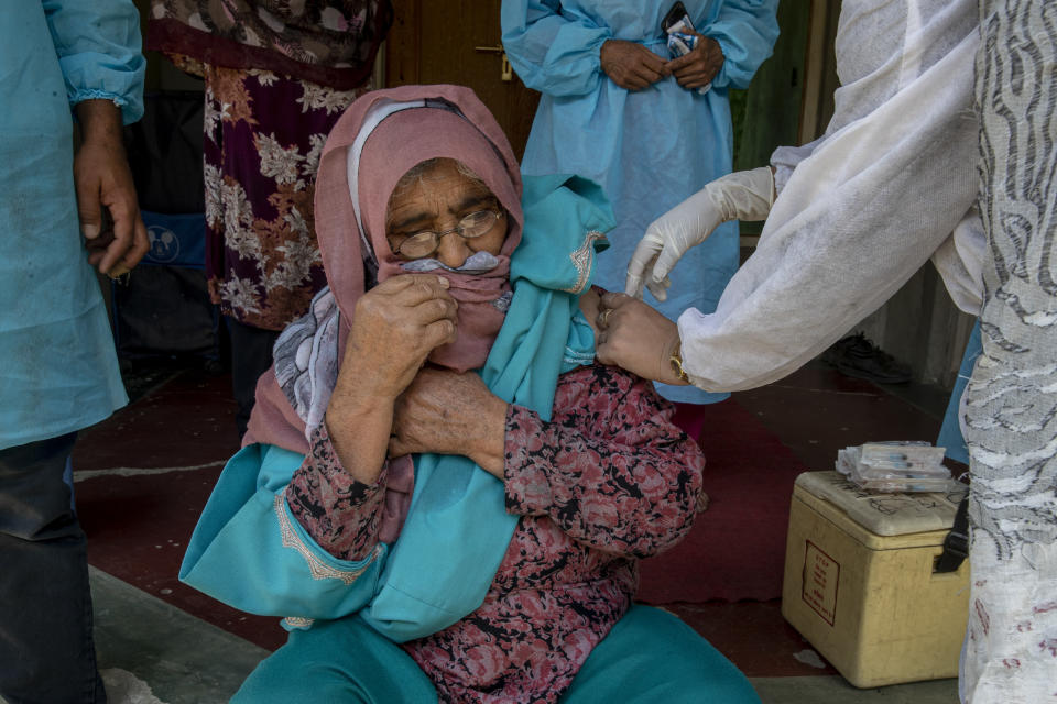 A health worker administers the AstraZeneca vaccine for COVID-19 to a Kashmiri woman after persuading her to take the shot in Tral village south of Srinagar, Indian controlled Kashmir, Saturday, June 5, 2021. (AP Photo/ Dar Yasin)