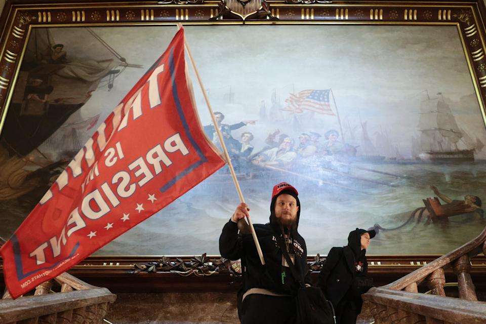 A protester holds a Trump flag inside the US Capitol Building near the Senate Chamber on January 06, 2021 in Washington, DC. (Win McNamee/Getty Images)