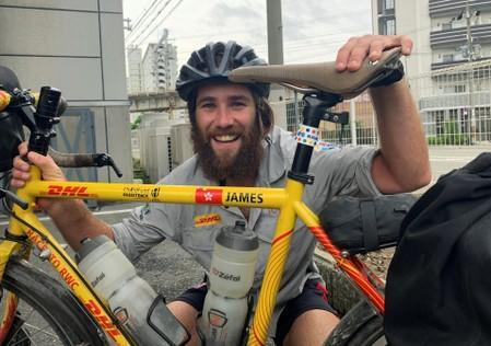 Cyclists James Owens poses with a bicycle after reaching Osaka, following almost 20,000 kilometre trip from London to deliver Rugby World Cup whistle, in Osaka