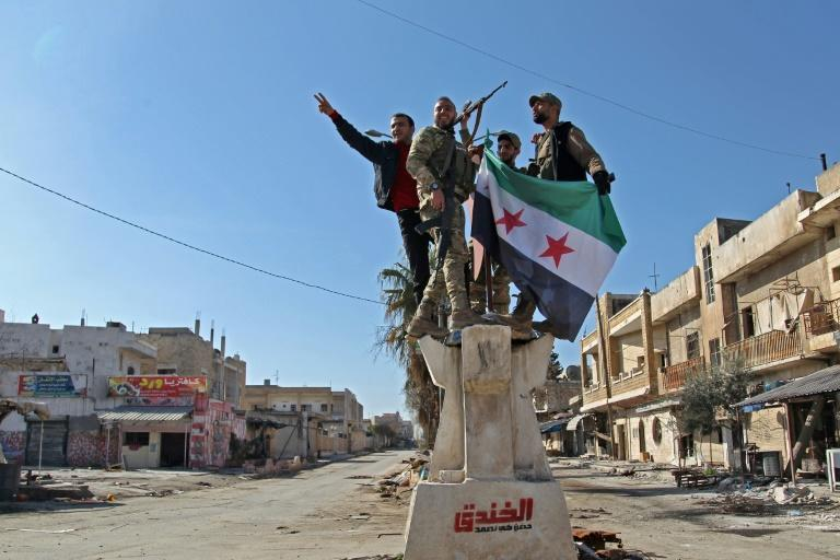 Turkey-backed Syrian fighters celebrate in the town of Saraqeb in the eastern part of the Idlib province in northwestern Syria (AFP Photo/Abdulaziz KETAZ)