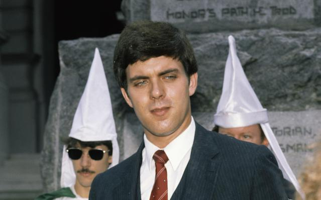 The Imperial Wizard of the National Knights of the Ku Klux Klan, Don Black, in 1982, wearing a suit and tie, with white-gowned Klan members in the background. (Photo: Bettmann Archive via Getty Images)