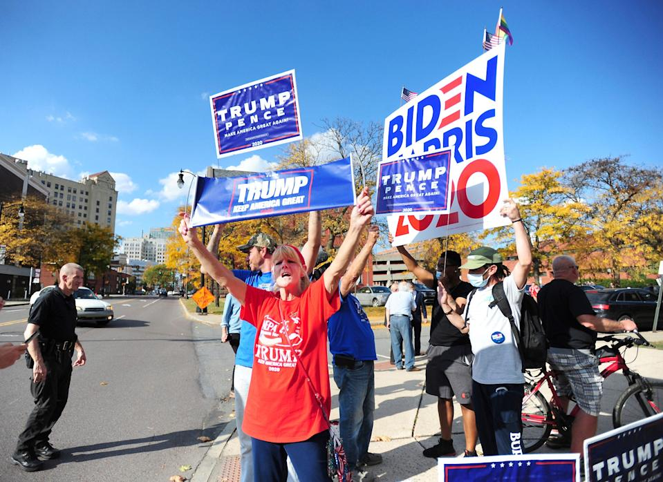 President Donald Trump supporters and Democratic presidential candidate Joe Biden supporters square off in front of Penn Place office building in Wilkes-Barre, Pa., Thursday, Oct. 22, 2020. The Luzerne County Election Bureau is located inside Penn Place where early walk-in voting has started.