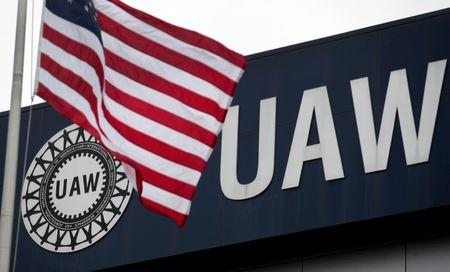 FILE PHOTO: An American flag flies in front of the United Auto Workers union logo  in Detroit