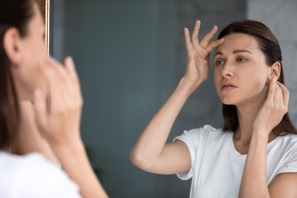 Anxious woman looking in mirror, standing in bathroom, upset attractive female touching forehead with finger, confused about wrinkles or acne, thinking about face lifting procedure or spa