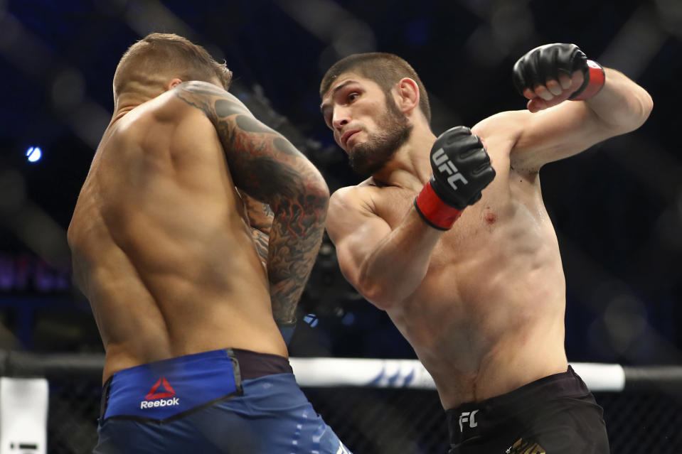 FILE - In this Sept. 7, 2019, file photo, Russia's Khabib Nurmagomedov, right, fights with Dustin Poirier, of Lafayette, La., during a lightweight title mixed martial arts bout at UFC 242 in Yas Mall in Abu Dhabi, United Arab Emirates. Nurmagomedov will risk his unbeaten record and his UFC lightweight title against interim champion Justin Gaethje in the main event of UFC 254 in Abu Dhabi on Saturday, Oct. 24, 2020. (AP Photo/Mahmoud Khaled, File)