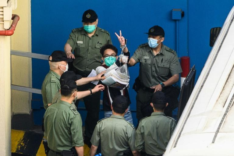 Pro-democracy activist Figo Chan (C) gestures as he walks to a Hong Kong Correctional Services van before being driven to the District Court