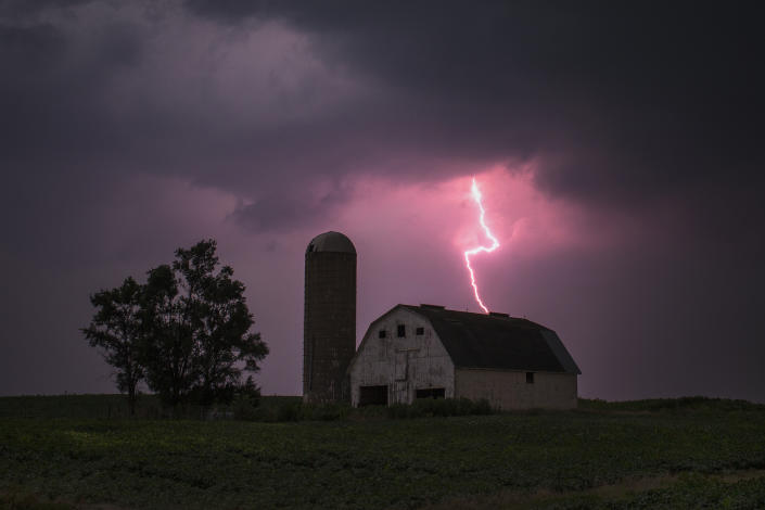 Lighting strikes over a barn surrounded by a soybean crop in Donnellson, Iowa, July 13, 2012. U.S. ranchers are rushing to sell off some of their cattle as the worst drought in nearly 25 years dries up pastures, thins hay supplies and sends feed costs sky-rocketing. The drought in the Midwest follows another one last year in the southern Plains. REUTERS/Adrees Latif