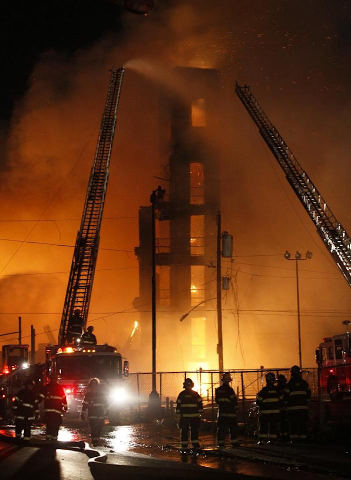Firefighters battle a fire in a warehouse on York Street near Kensington Avenue, early Monday, April 9, 2012, in Philadelphia. Officials say the fire claimed the lives of two Philadelphia firefighters after a wall collapsed inside an adjacent building where the two men were trying to halt the fire's progress. (AP Photo/Joseph Kaczmarek)