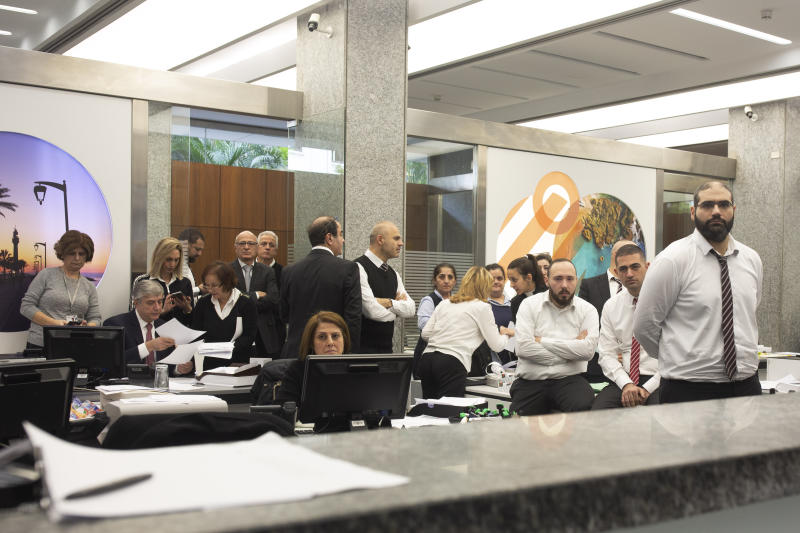 Bank employees watch anti-government protesters shout slogans inside a branch of Bank Audi on Monday, Dec. 30, 2019 in Beirut, Lebanon. (AP Photo/Maya Alleruzzo)