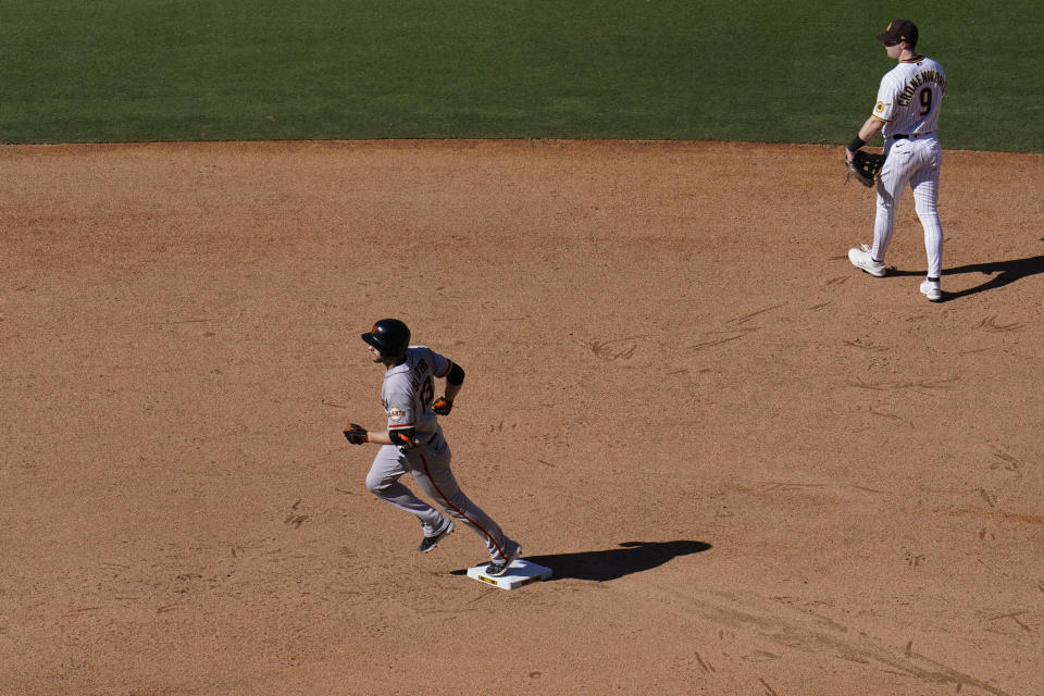 San Francisco Giants' Austin Slater, left, rounds second base after hitting a home run as San Diego Padres second baseman Jake Cronenworth, right, looks on during the sixth inning of a baseball game Thursday, Sept. 23, 2021, in San Diego. (AP Photo/Gregory Bull)