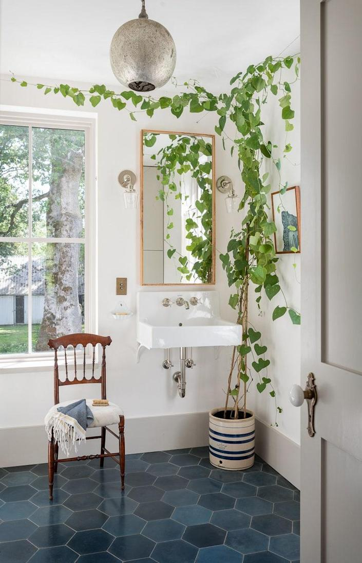 In the primary bathroom, the Dutchman's pipe vine adds an added hint of freshness. The custom wall sconces are by Schoolhouse Electric.