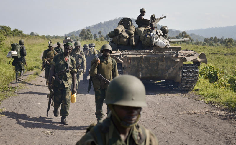 """FILE - In this Sunday, Oct. 27, 2013 file photo, Congolese army soldiers march past a tank aimed towards Kibumba Hill, which was occupied by M23 rebels, around 25kms from the provincial capital Goma, in eastern Congo. A Congolese rebel group whose fighters retreated into Uganda after being hammered by U.N.-backed Congolese government forces """"can still regroup,"""" a Ugandan government spokesman said Tuesday, Nov. 12, 2013. The warning came after Congolese government officials delayed signing a peace accord with the insurgents. (AP Photo/Joseph Kay, File)"""