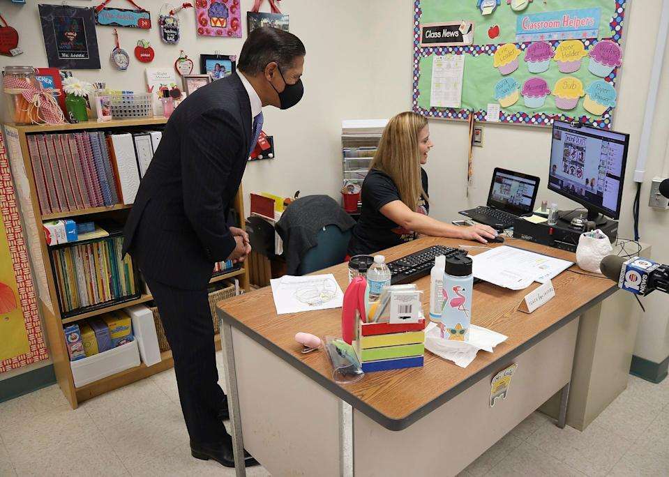 In this Aug. 31 file photo, Miami-Dade County Public Schools Superintendent Alberto Carvalho leans over to greet students remotely during a visit to Vanessa Acosta's first grade class at the Bob Graham Education Center in Miami Lakes, Fla.