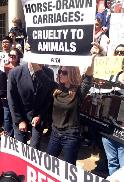"""Jillian Michaels, from """"The Biggest Loser,"""" holds up a sign on City Hall steps at a PETA-sponsored rally protesting horse carriages, in New York. The mayor, Bill de Blasio, also supports banning the carriages. (AP Photo/Jonathan Lemire)"""