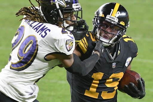 Pittsburgh Steelers wide receiver JuJu Smith-Schuster (19) tries to fend off Baltimore Ravens cornerback Tramon Williams after making a catch during the second half of an NFL football game Wednesday, Dec. 2, 2020, in Pittsburgh. (AP Photo/Don Wright)