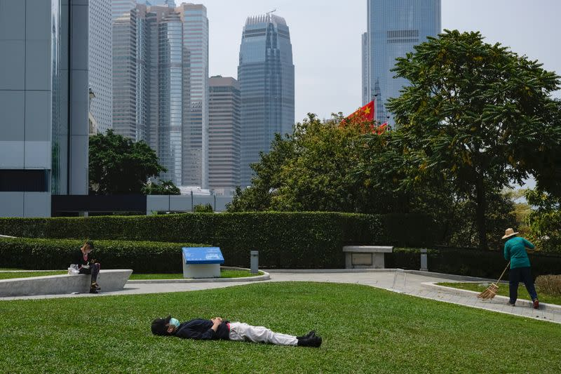 FILE PHOTO: A man with a protective face mask takes a nap during lunch breaks at the financial Central district, following the coronavirus disease (COVID-19) outbreak, in Hong Kong