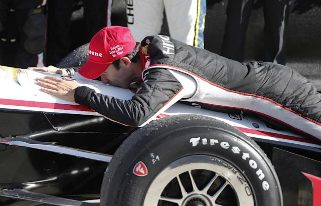 Helio Castroneves kisses his car in the winners circle after his victory in the second race of the IndyCar Detroit Grand Prix auto racing doubleheader in Detroit Sunday, June 1, 2014. (AP Photo/Bob Brodbeck)