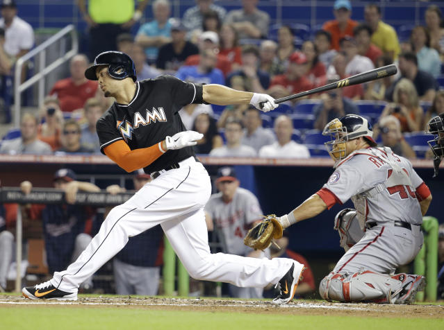 Miami Marlins' Giancarlo Stanton, left, strikes out to send the first inning as Washington Nationals catcher Wilson Ramos (40) looks on during a baseball game, Monday, July 28, 2014, in Miami. (AP Photo/Lynne Sladky)
