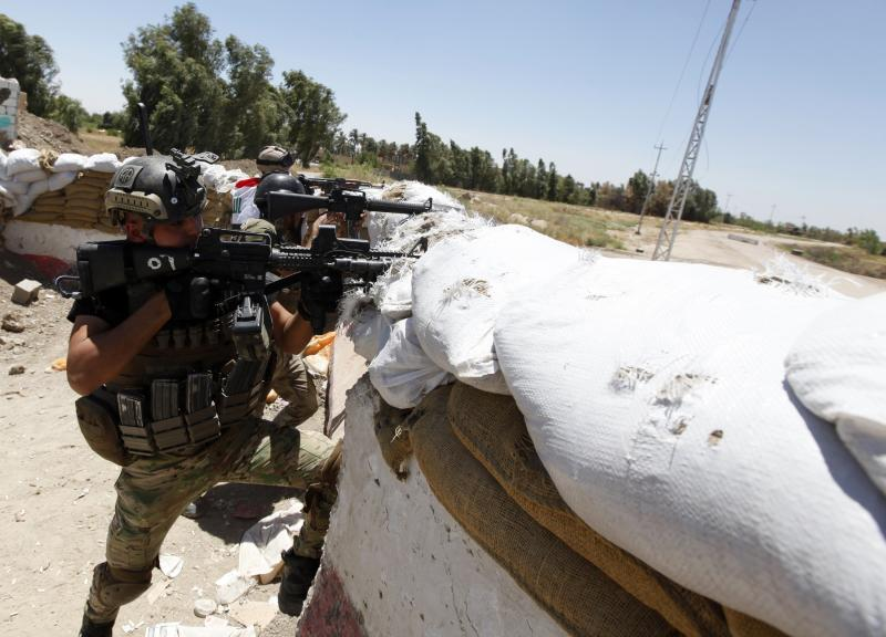 Members of the Iraqi security forces take positions during clashes with ISIL, west of Baghdad