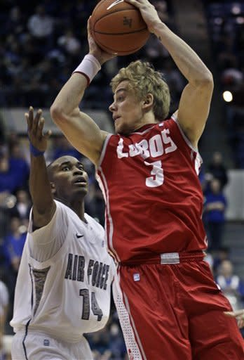 New Mexico's Hugh Greenwood, right, looks to pass while covered by Air Force's Michael Lyons during the second half of an NCAA college basketball game in Air Force Academy, Colo., Saturday, March 9, 2013. (AP Photo/Brennan Linsley)