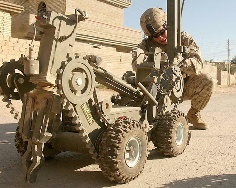 A robot on wheels is attended to by a soldier in combat gear