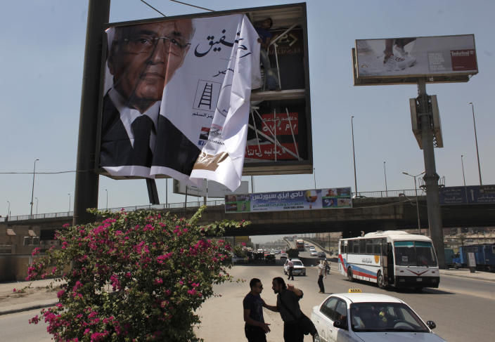 "A laborer installs an election poster for Egyptian presidential runoff candidate, Ahmed Shafiq, on the side of a highway in Cairo, Egypt, Monday, June 11, 2012. Shafiq faces the Muslim Brotherhood's candidate, Mohamed Morsi, in the June 16-17 runoff that could mean the difference between a secular state or one in which a hidden Islamist agenda slowly takes root. Arabic, partially shown, reads, ""Ahmed Shafiq, President for Egypt."" (AP Photo/Nasser Nasser)"