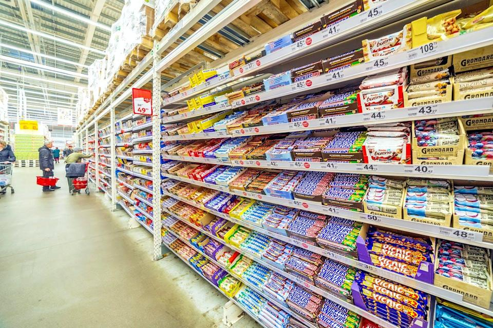 A long aisle with shelves of chocolate bars.