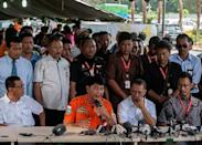 Sunu Widiatmoko (R), the president of Indonesia-AirAsia, listens as Surabaya search and rescue chief Hernanto (2nd L) speaks during a press conference outside the crisis-centre set up at Juanda International Airport in Surabaya