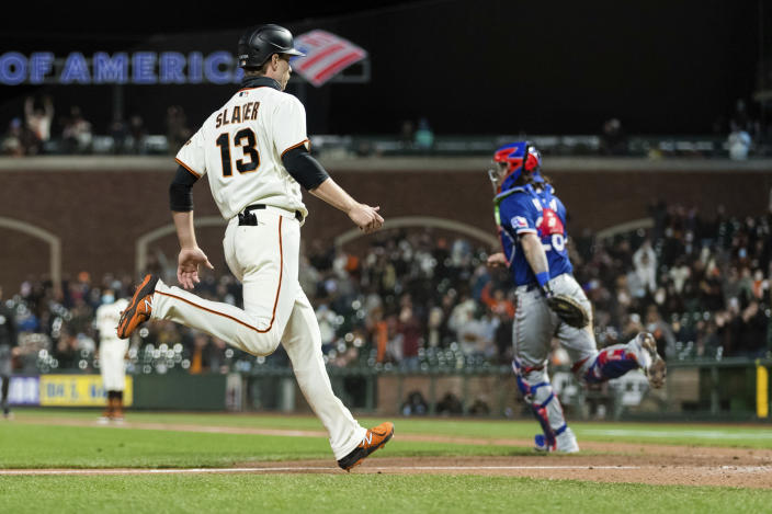 San Francisco Giants' Austin Slater (13) scores a run against the Texas Rangers during the seventh inning of a baseball game in San Francisco, Monday, May 10, 2021. (AP Photo/John Hefti)