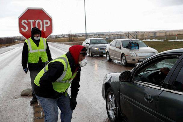 PHOTO: Steve Yankton and Nathaniel Badmilk speak to drivers during a lockdown at the entrance to the Pine Ridge Indian Reservation in Pine Ridge, S.D., April 15, 2020. (Andrew Hay/Reuters)