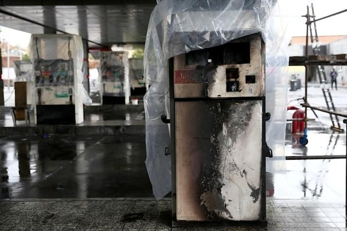 FILE PHOTO: Destroyed petrol pumps are pictured at a gas station, after protests against increased fuel prices, in Tehran