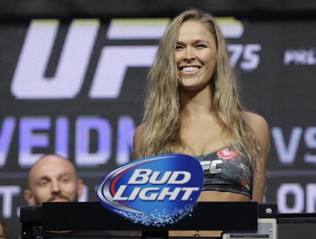 Ronda Rousey stands on the scale during a weigh-in for the UFC 175 mixed martial arts event at the Mandalay Bay, Friday, July 4, 2014, in Las Vegas. Rousey is scheduled fight Alexis Davis in a women's bantamweight title fight on Saturday in Las Vegas. (AP Photo/John Locher)