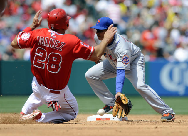 New York Mets shortstop Ruben Tejada, right, catches the ball ahead of Los Angeles Angels' Raul Ibanez, left, to force an out after Angels' Kole Calhoun hit a ground ball to fielder's choice during the third inning of a baseball game in Anaheim, Calif., Sunday, April 13, 2014. (AP Photo/Kelvin Kuo)