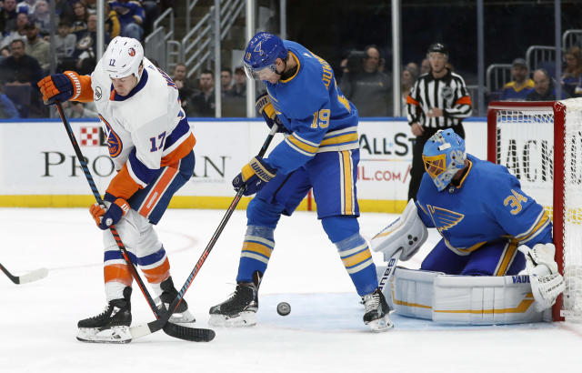 New York Islanders' Matt Martin (17) and St. Louis Blues' Jay Bouwmeester (19) vie for a loose puck as Blues goaltender Jake Allen (34) watches during the first period of an NHL hockey game Saturday, Jan. 5, 2019, in St. Louis. (AP Photo/Jeff Roberson)