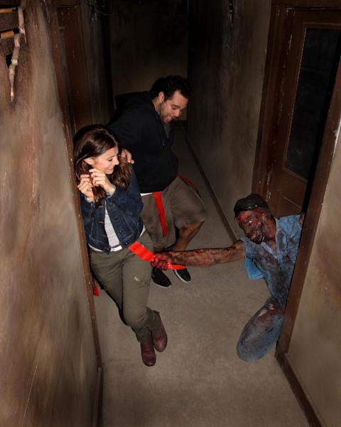This August 2013 image provided by Shocktoberfest shows an actor portraying a zombie grabs a flag from the belt of someone walking through the Prison of the Dead Escape, part of the Shocktoberfest attraction in Reading, Pa. Halloween-themed attractions are becoming more interactive, with guests no longer merely passive observers walking through a haunted house, but often engaging in a game or challenge as part of the experience. (AP Photo/Shocktoberfest)