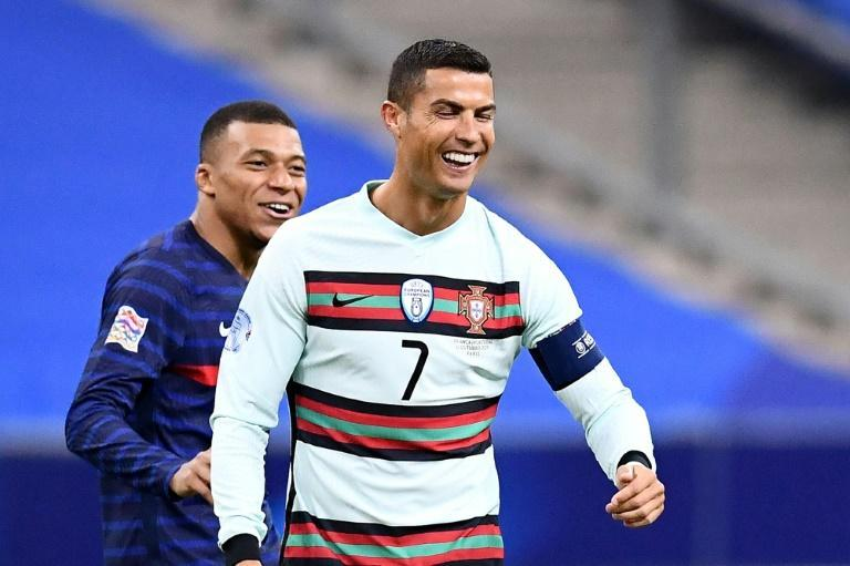 Cristiano Ronaldo and Kylian Mbappe share a joke during the goalless draw between France and Portugal last month. The sides meet again in a potentially decisive encounter in Lisbon this weekend