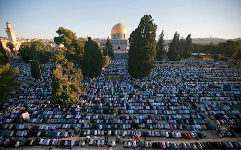 Palestinian Muslim men perform the morning Eid Al-Fitr prayer in front of the Dome of Rock at the Al-Aqsa Mosque compound in 2013 - Credit: AHMAD GHARABLI/AFP/Getty Images