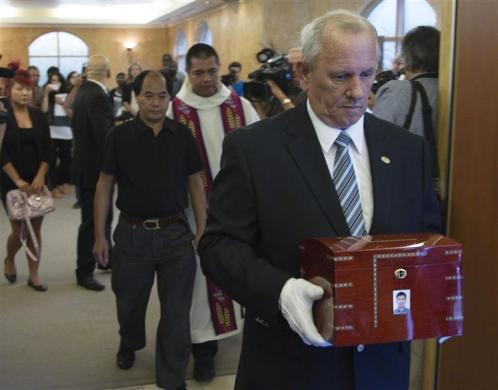 Dirang Lin (in black), father of slain student Jun Lin follows the urn after funeral services in Montreal, July 26, 2012.