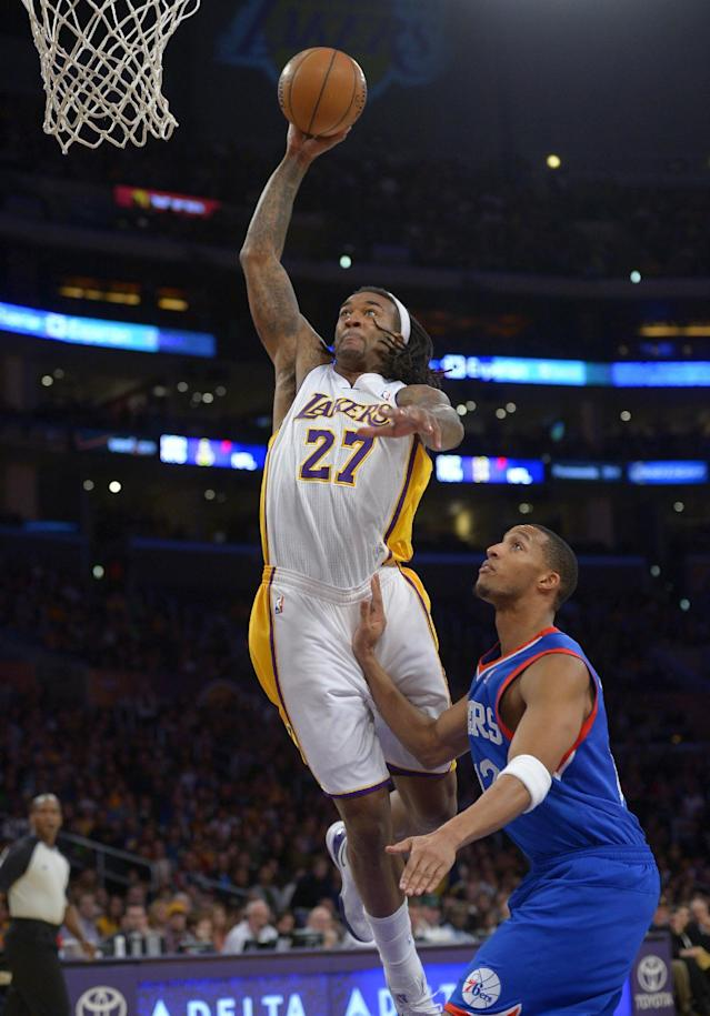 Los Angeles Lakers center Jordan Hill, left, goes up for a dunk as Philadelphia 76ers forward Evan Turner during the first half of an NBA basketball game, Sunday, Dec. 29, 2013, in Los Angeles. (AP Photo/Mark J. Terrill)