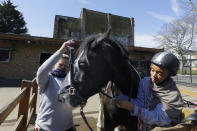 Tasneem Aly, right, and General manager Naomi Howgate take the harness off Bailey after a riding lesson at Ebony Horse Club in Brixton, south London, Sunday, April 18, 2021. In the midst of south London's hustle and bustle, only a 10-minute walk from a subway station, is a school where children are encouraged to horse around. The Ebony Horse Club provides 140 rides per week to children in the local community offering them the opportunity to learn important life skills along with horseback riding. (AP Photo/Kirsty Wigglesworth)