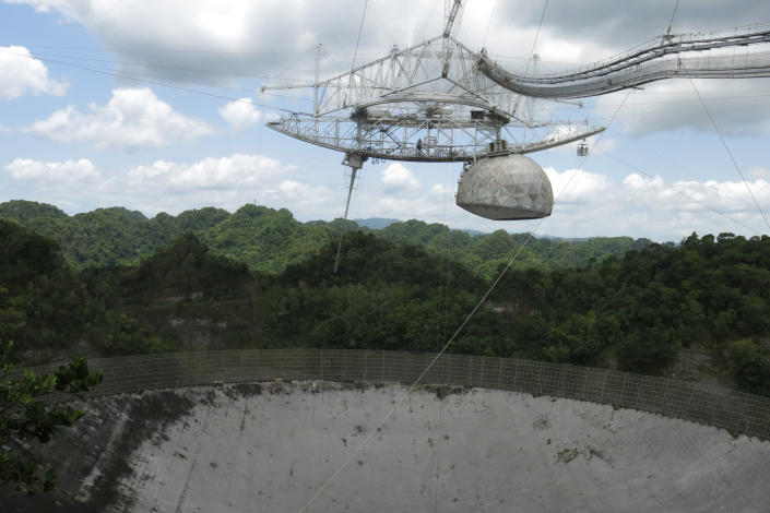 FILE - This July 13, 2016 file photo shows one of the largest single-dish radio telescopes at the Arecibo Observatory in Arecibo, Puerto Rico. Giant, aging cables that support the radio telescopes are slowly unraveling in this U.S. territory, threatening scientific projects that researchers say can't be done elsewhere on the planet. (AP Photo/Danica Coto, File)
