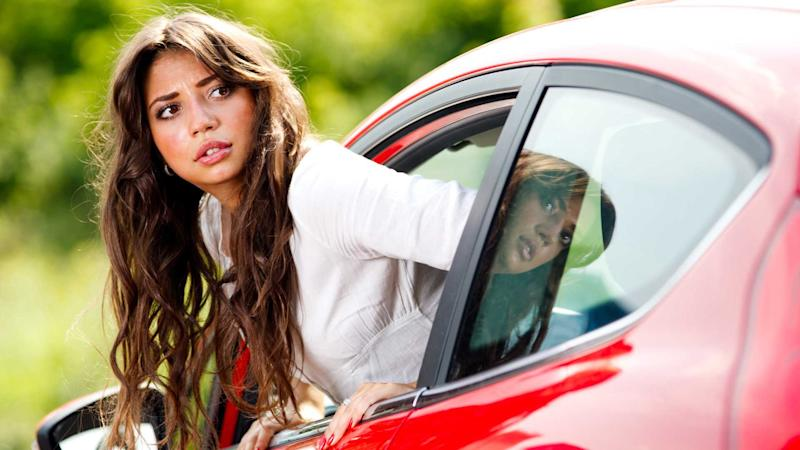 Worried woman leaning out window and looking at back of car