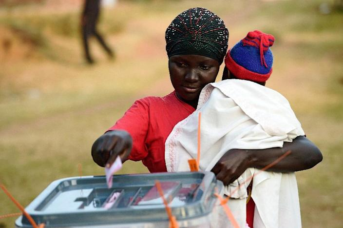 A woman holding her child casts her ballot during Uganda's national elections in Kampala on February 18, 2016 (AFP Photo/Carl de Souza)