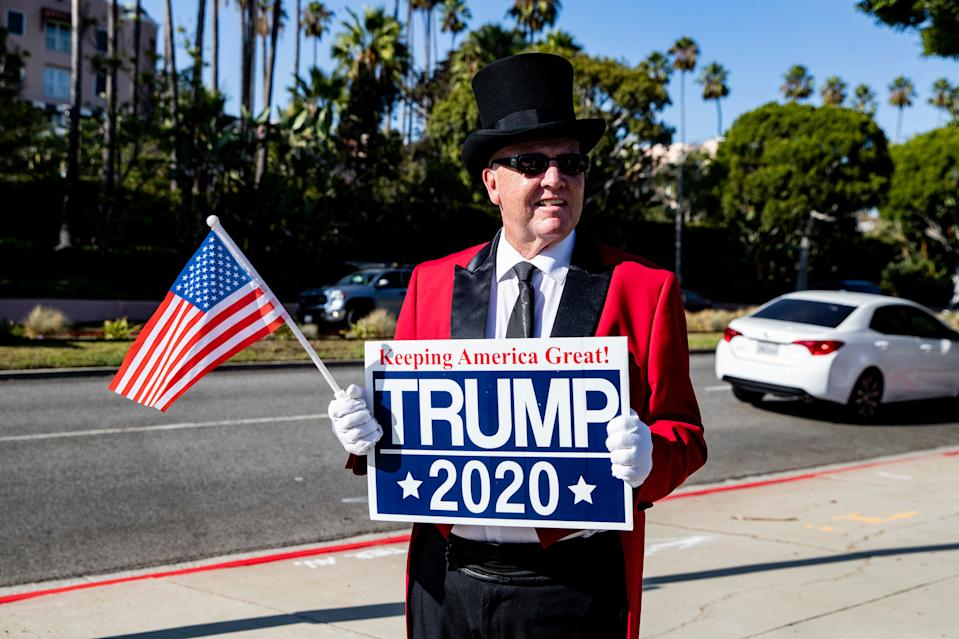 A Trump supporter holds a sign as he waits for the arrival of President Donald Trump in front of the Beverly Hills Hotel in Beverly Hills, Calif. Sept. 17, 2019. Trump is on a two-day trip to California to raise money for his 2020 election campaign. (Photo: Etienne Laurent/Epa-Efe/Shutterstock)