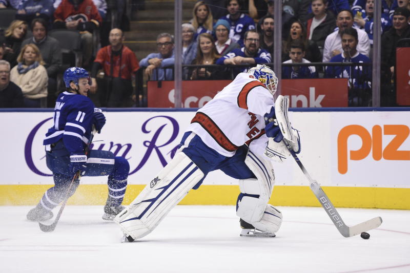Carolina Hurricanes emergency goalie David Ayres, right, comes out of his net to play the puck against the Toronto Maple Leafs during second-period NHL hockey action in Toronto, Saturday, Feb. 22, 2020. Ayres, who serves as the Toronto Marlies' ice resurfacer driver, replaced Petr Mrazek in-net after a delay in action. (Frank Gunn/The Canadian Press via AP)
